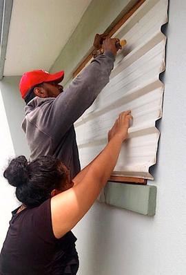 A supplied image shows locals covering windows to office buildings as part of preparations for Cyclone Gita in the Tonga capital of Nuku'alofa