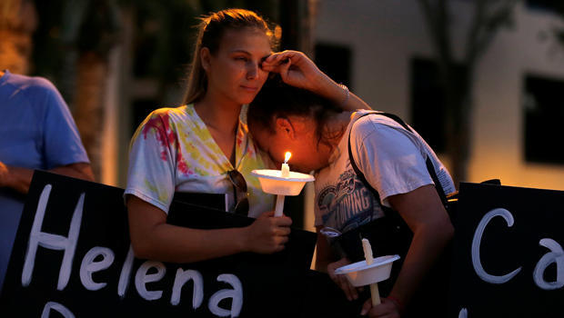 Tori Stetzer and Taylor Miler, both of Parkland, react during a candlelight vigil for victims of the shooting in Parkland, Florida at Florida Atlantic University in Boca Raton