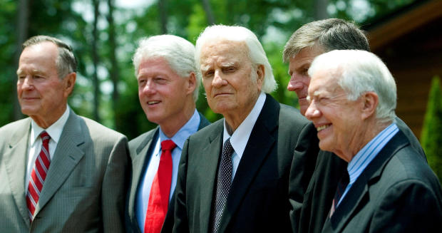 Former Presidents George H.W. Bush, left; Bill Clinton, second left; and Jimmy Carter, right, pose with evangelist Billy Graham and his son Franklin Graham, second right, before the Billy Graham Library dedication on the campus of the Billy Graham Evangel