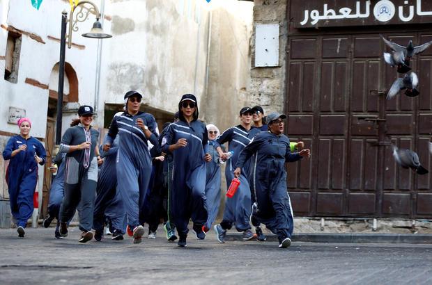 Women run during an event marking International Women's Day in Old Jeddah