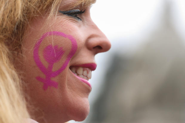 Woman smiles at nationwide feminist strike on IWD at Cibeles Square in Madrid