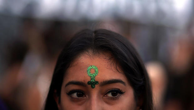 A woman has the symbol for women painted on her face during a demonstration on International Women's Day in Buenos Aires