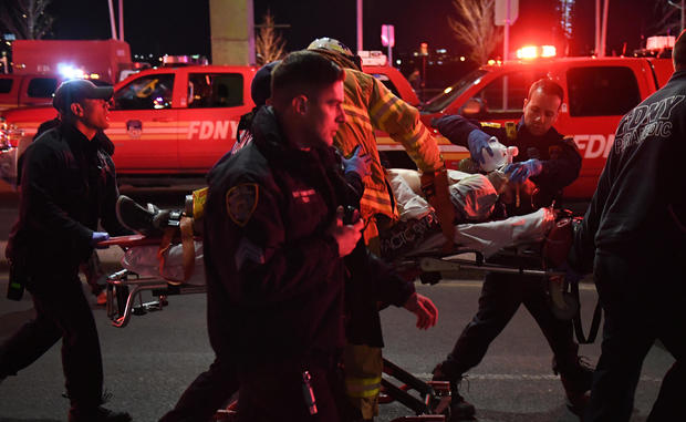 Paramedics and members of the NYFD perform CPR on a victim of a helicopter that crashed into the East River in New York