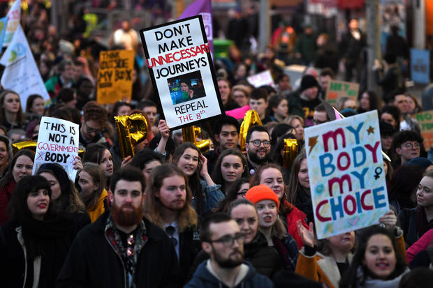 Demonstrators hold posters as they march for more liberal Irish abortion laws, in Dublin