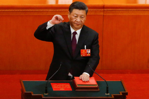 Chinese President Xi Jinping pledges an oath to the Constitution after being confirmed president for another term during the National People's Congress at the Great Hall of the People in Beijing