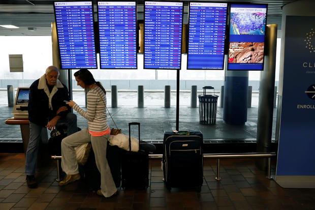 Air travelers sit with baggage next to Delta flight monitors showing canceled flights at LaGuardia Airport in New York March 21, 2018.