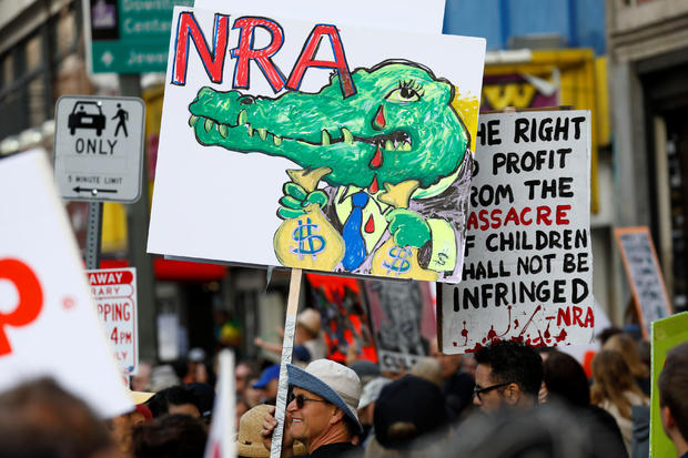 """People walk with signs against the NRA during """"March for Our Lives"""", an organized demonstration to end gun violence, in downtown Los Angeles"""