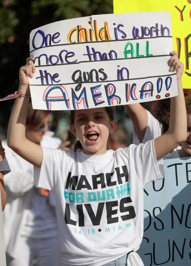 """A girl holds a sign while rallying in the street during the """"March for Our Lives"""" demanding stricter gun control laws at the Miami Beach Senior High School, in Miami"""