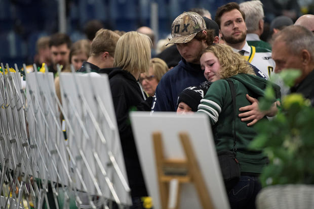 People look at photos of the victims during a vigil at the Elgar Petersen Arena, home of the Humboldt Broncos, to honour the victims of a fatal bus accident in Humboldt