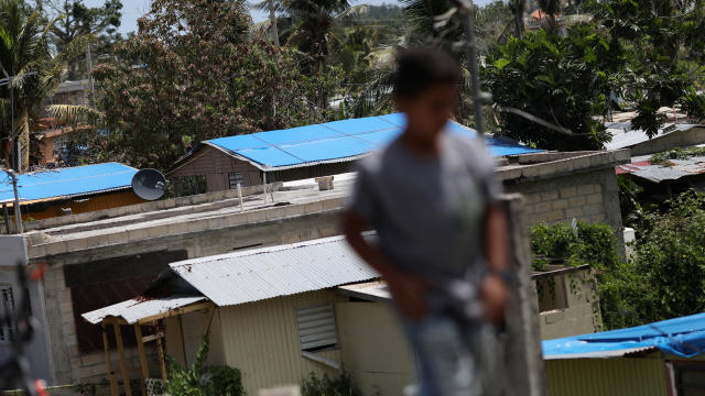 A boy walks near houses with plastic sheets replacing roofs hit by Hurricane Maria in September, in a neighborhood in Canovanas, Puerto Rico, April 10, 2018.