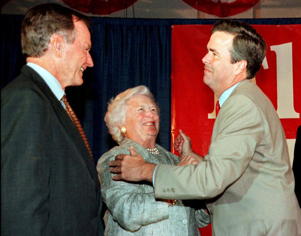 FILE PHOTO: Former President George Bush (L) and wife Barbara congratulate their youngest son Jeb Bush at the Republican gubernatorial candidate's victory party in Miami