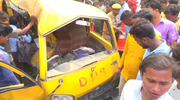 People gather around a school bus after colliding with a train in Uttar Pradesh