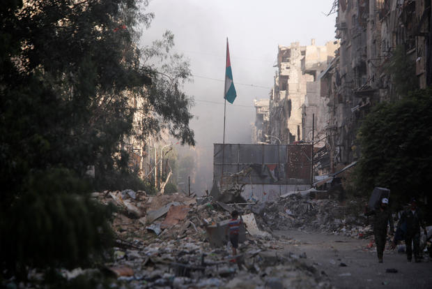 A boy stands on the rubble of damage buildings in Yarmouk Palestinian camp in Damascus