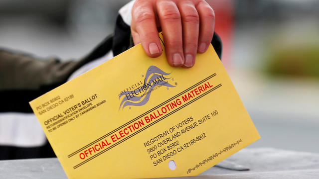 FILE PHOTO: A poll worker places a mail in ballot into a voting box as voters drop off their ballot in the U.S. presidential primary election in San Diego, California