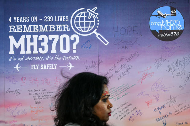 A woman walks past a banner bearing solidarity messages for passengers of the missing Malaysia Airlines Flight 370 during a memorial event in Kuala Lumpur on March 3, 2018, ahead of the fourth anniversary of the ill-fated plane's disappearance.