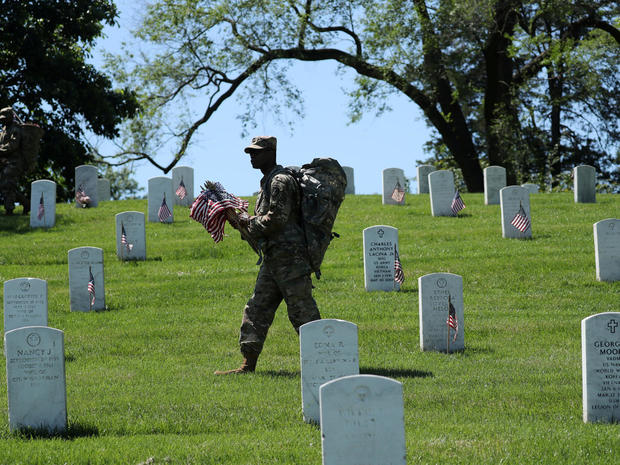 A U.S. Army soldier of the 3rd United States Infantry Regiment places U.S. flags on graves at Arlington National Cemetery