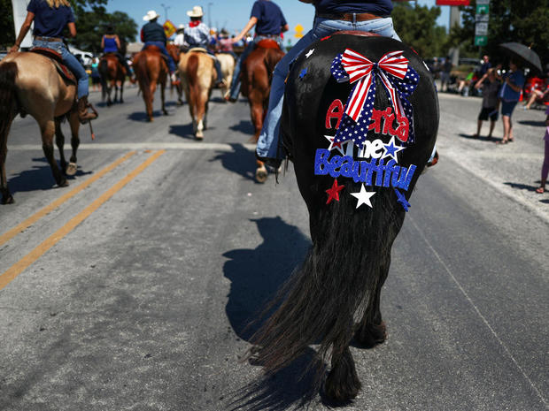Sign hangs from tail of horse during Memorial Day Parade in Bandera, Texas