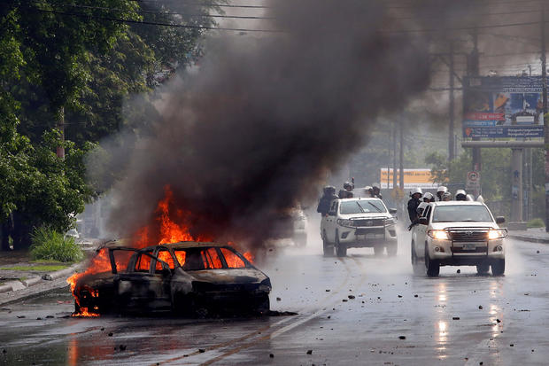 Riot police officers travel past a burning car during clashes with the anti-government protesters in Managua, Nicaragua