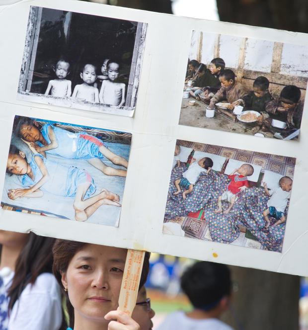 A woman holds up a poster with photos fr