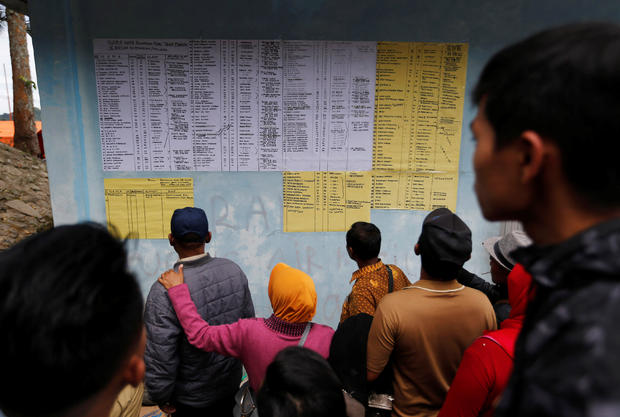 Villagers and relatives look at a list of missing passengers from Monday's ferry accident at Lake Toba in Simalungun