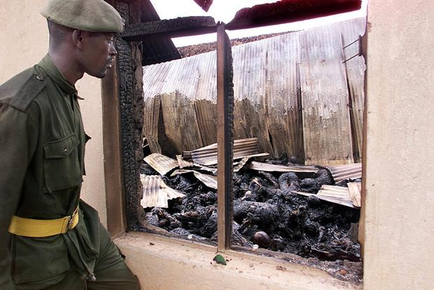 A soldier views the burned remains of up to 250 Ug