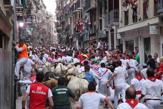 Revellers sprint in front of bulls and steers during the sixth running of the bulls of the San Fermin festival in Pamplona
