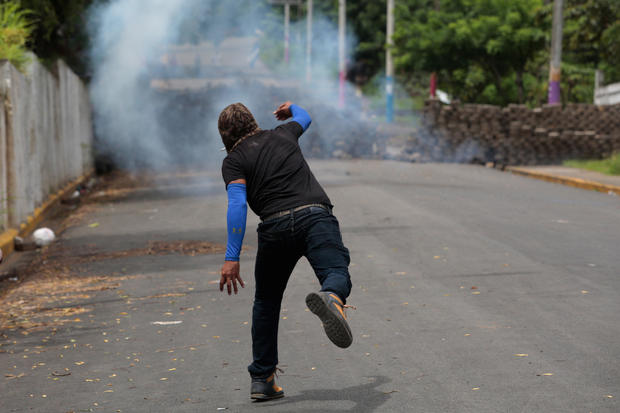 Demonstrator throws a homemade device during the funeral service of Jose Esteban Sevilla Medina, who died during clashes with pro-government supporters in Monimbo