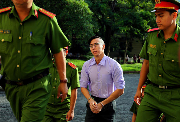 U.S. citizen Will Nguyen is escorted by police before his trial at a court in Ho Chi Minh city