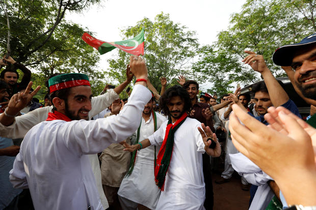 Supporters of cricket star-turned-politician Imran Khan, chairman of Pakistan Tehreek-e-Insaf (PTI), celebrate outside his residence in Islamabad, Pakistan, a day after polling in the general election