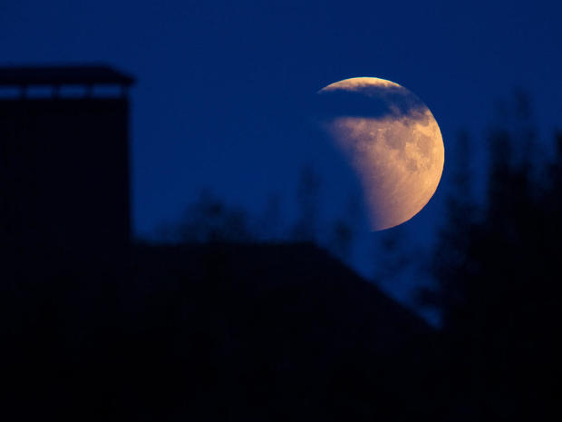 Full moon during an eclipse rises behind a house on the outskirts of Minsk