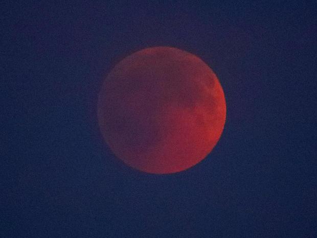 A lunar eclipse is seen through clouds in Berlin