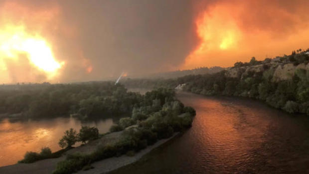 Smoke and flames are seen as a wildfire spreads through Redding, California