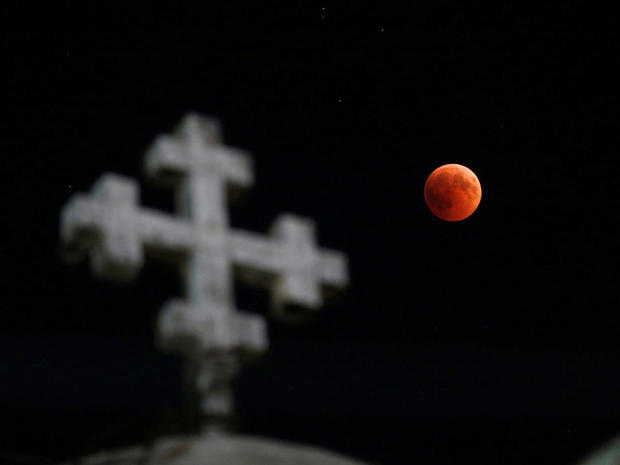 The moon is seen during a lunar eclipse over the Coptic Orthodox Patriarchate Church in Amman