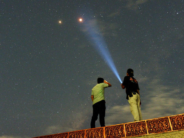 Residents look at Mars alongside the lunar eclipse in Padang