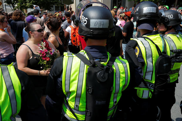 Police in riot gear block demonstrators at the site where Heather Heyer was killed in Charlottesville