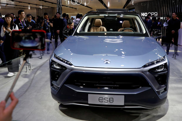FILE PHOTO: Visitors check NIO ES8 displayed during a media preview of the Auto China 2018 motor show in Beijing