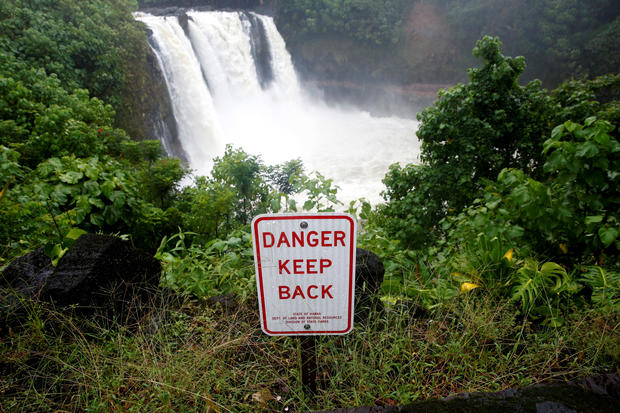 A sign warns of danger at a waterfall swollen by rain from Hurricane Lane in Hilo