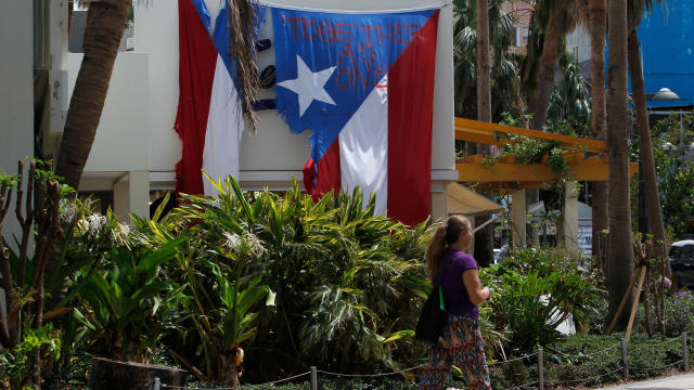 """""""Together as One"""" reads on a torn Puerto Rican flag hanging from a hotel in the tourist zone of el Condado in San Juan, Puerto Rico, on Oct. 4, 2017."""