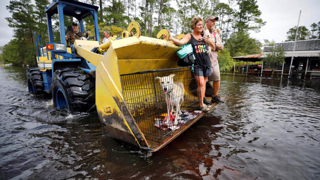 Jimmy Shackleford of Burgaw transports his son Jim Shackleford and his wife Lisa, and their pets in the bucket of his tractor as the Northeast Cape Fear River breaks its banks