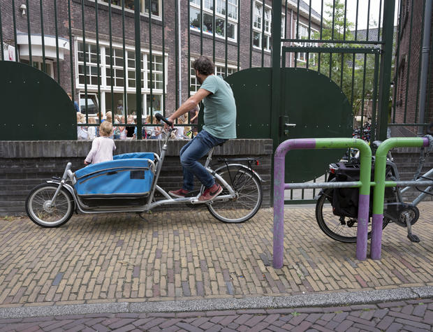 father waits with cargo bike in dutch town of delft