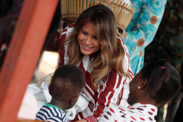 U.S. first lady Melania Trump greets a child during a visit to a hospital in Accra