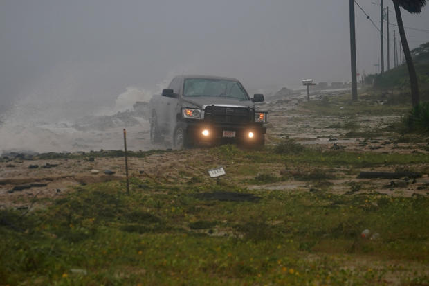 A truck drives along a road that has been washed out as Hurricane Michael comes ashore in Alligator Point