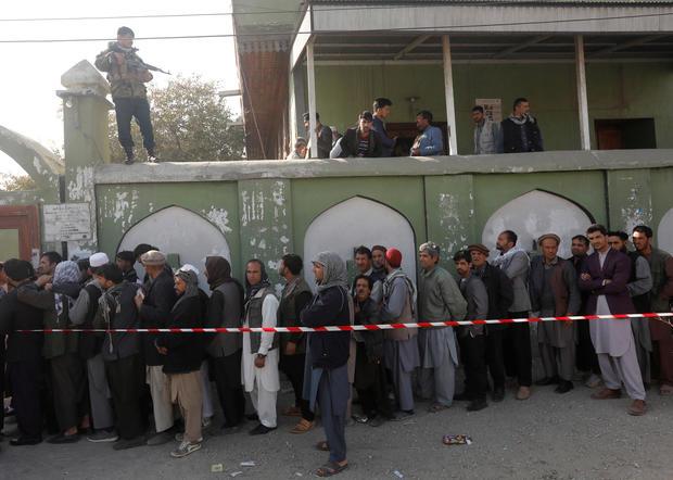 在喀布尔的一个投票站举行的议会选举中,阿富汗男子排队投票
