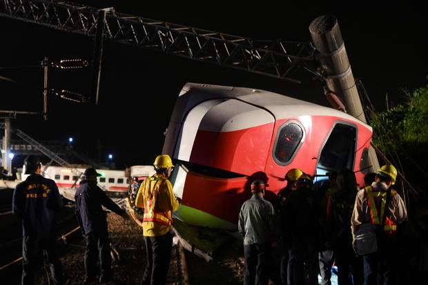 Rescuers search an overturned train in Yilan