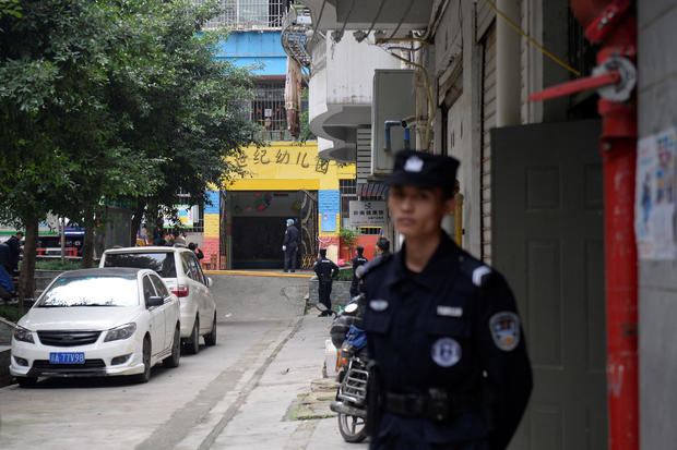 Police officers are seen outside the gate of a kindergarten where a woman armed with a kitchen knife attacked children, in Chongqing