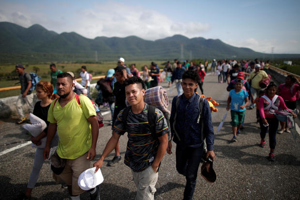 Migrants, traveling with a caravan of thousands from Central America en route to the United States, walk along the highway to Juchitan from Santiago Niltepec