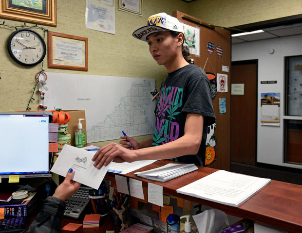Terrell Elk, 18, votes for the first time by delivering his absentee ballot to the Sioux County auditor's office on the Standing Rock Reservation in Fort Yates, North Dakota, Oct. 26, 2018.