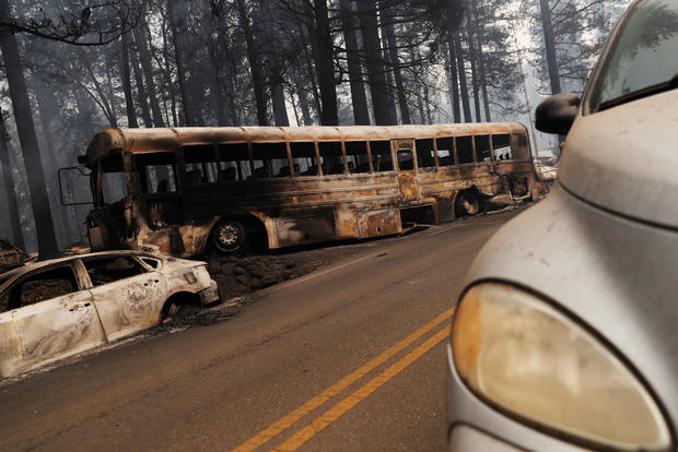 An abandoned and burned school bus is seen on Skyway during the Camp Fire in Paradise
