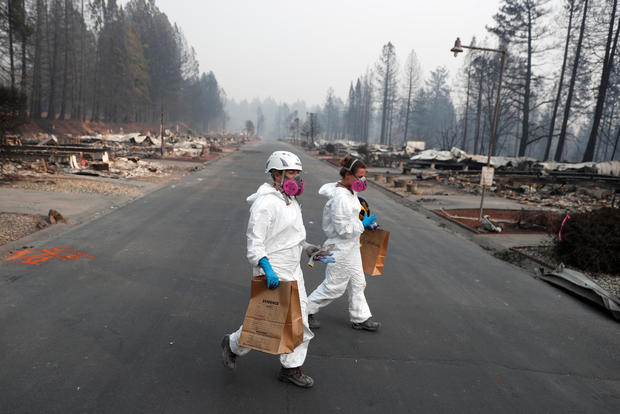 Forensic anthropologists Kyra Stull, center, and Tatiana Vlemincq recover human remains from a trailer home destroyed by the Camp Fire in Paradise, California, Nov. 17, 2018.