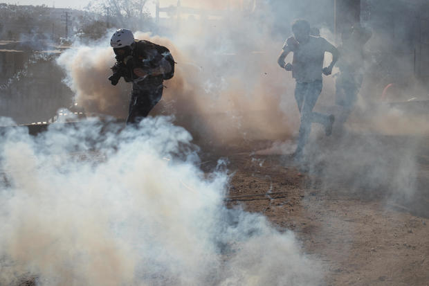 A photojournalist is surrounded in a cloud of tear gas released by U.S. Customs and Border Protection (CBP) after migrants, part of a caravan of thousands from Central America, attempted to illegally cross the border into the United States from Tijuana
